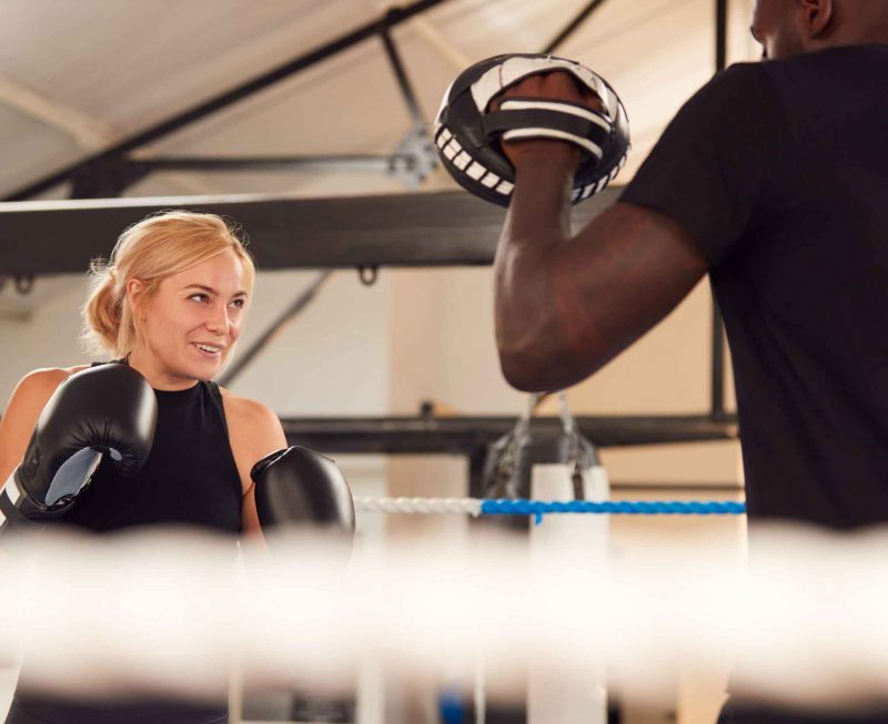 male-personal-trainer-sparring-with-female-boxer-i-URYN999